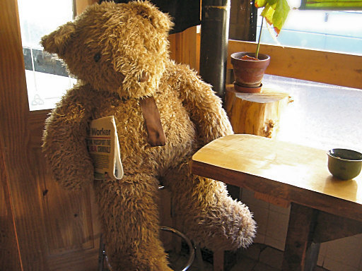 huge Teddy Bear sitting in an Internet cafe