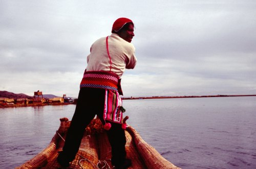 Uro-indian steering a boat on lake Titicaca